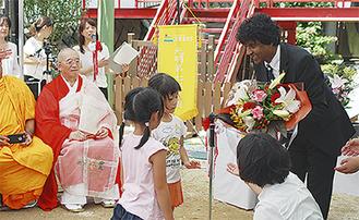 園児から花束を受け取るダンミカ大使(右)。左から4番目が足利理事長