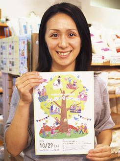 チラシを持つ実行委員の一人、田口直美さん