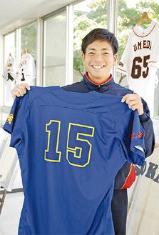 田中選手のユニフォームをもつマネージャーの戸田敬さん。同大出身のプロ野球選手(現役含む)のユニフォームが飾られている寮にて