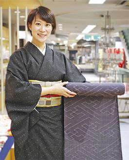 結城紬を持つ荒井社長。着ている結城紬は「祖母のお下がり」だそう