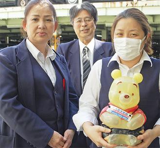 熊の募金箱を手にする八王子交通のスタッフ(後方が内田所長)