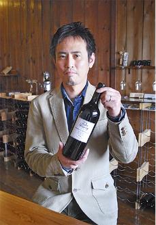 自社で手掛けたワインを持つ大澤さん