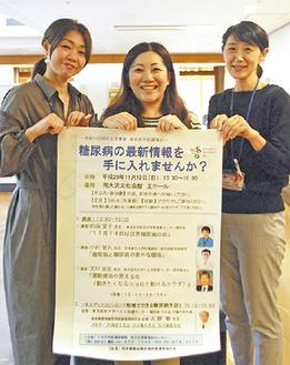 イベントのポスターを持つスタッフ