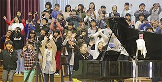 踊る児童とピアノを弾く李枝さん