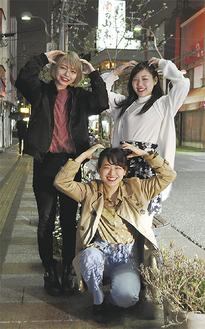 みずき通りで「思い出」のポーズを披露するトリオの渡邉さん、斎藤さん、長田さん(左から)