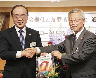 手を取り合う佐藤会長(左)と鈴木会長(右)