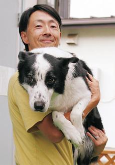 愛犬のコテツを抱く伊藤さん