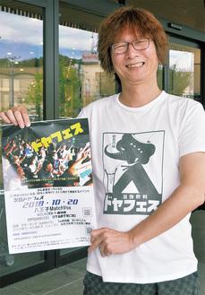 「ドヤ顔」でイベントのポスターを持つ松崎さん。実行委員会の委員長を務める