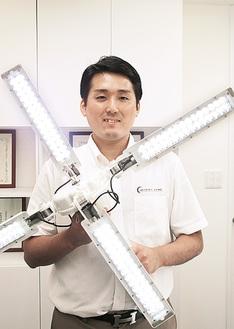 120個のLEDが光るX-terasoを持つ平塚さん。「MIRAI-LABOは、常識を覆す省エネ技術の提供を通じて、100年後を見据えた豊かな地球環境創りに貢献します」
