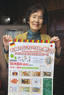 イベントのポスターを持つ、主催実行委員長の塚本回子さん。「私も当日聴くことができるのを楽しみにしています」