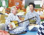 2011年7月、避難所で三味線を弾く艶子さん。右はめぐみさん=浅原須美さん撮影