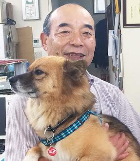 保護犬のビスクを抱き上げる石井さん