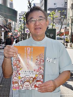 会場となる通りでチラシを持つ橋本会長