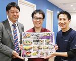 右から二階堂院長、新メニューを持つ石井店長、同院職員の青木司さん
