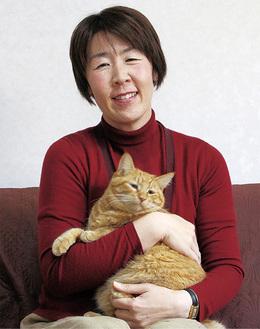 愛猫を抱き上げる野下さん