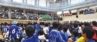 「ようこそ八王子へ!」。満席の開会式会場で石巻FCが紹介されたときの様子。スタンドで緑色の上着を着ているのが同チーム