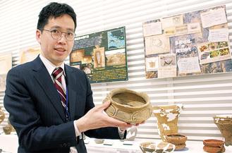 所属する博物館の土器を手にする甲田さん