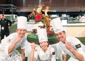 ▲作品をバックに銀メダルを喜ぶ日本代表の3人。左から小熊さん、西川さん、伊藤さん