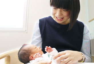 わが子と見つめ合う尋子さん。夫の和徳さんの出産までのフォローが心強かったと話している