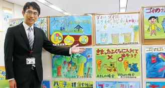 市内の小学生が描いたごみ減量を訴える絵画を指さす、市ごみ減量対策課の坂野優一課長