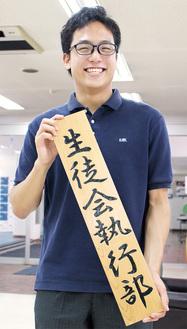 青春を傾けた生徒会の看板を手にする今池さん。昨年度まで代表を務めていた組織も団体の部大賞に選出された