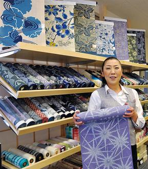 加賀染めの反物を持つスタッフの中田さん。仮店舗の1階は現在、浴衣を大々的に展開している