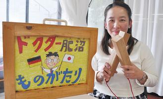 ▲拍子木を持ち紙芝居を案内する田中さん