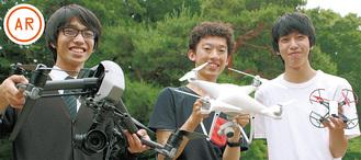 タイプの違うドローンを掲げる生徒たち(左から長坂さん、菅野翼さん、菅野暁鐘さん)