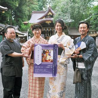 子安神社でイベントのポスターを持つイベント参加店の店主たち。右から2人目が実行委員長の杉野さん