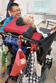 車椅子に座りトーンチャイムを鳴らす利用者。青いシャツが大谷さん