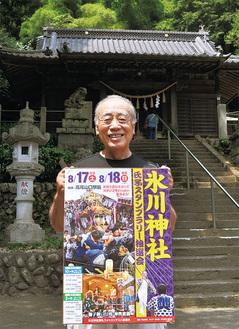 ポスターを持つ同神社責任役員の1人、青木勝一さん