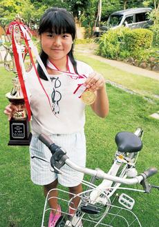 都大会の個人優勝のトロフィーとメダルを手に持つ佐藤さん。将来の夢は幼稚園の先生かイルカのトレーナーとのこと