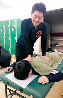 ロッカールームで選手に施術する矢崎さん