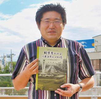 冊子を手にする村松さん