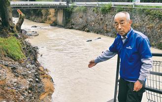 濁った浅川を案内する野村さん。流木により河岸はえぐられた