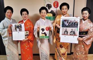 左から小サイズのカレンダーを持つ里菜さんと夕子さん、来年5月開催八王子をどりのチラシをもつあやめさん、大サイズを持つ小太郎さんと理子さん