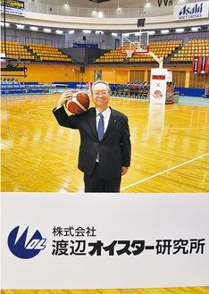 試合会場で掲示される看板を前に立つ渡辺社長