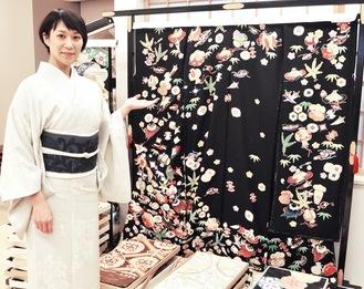 染め着物と織りの帯をまとい、縁起の良い「宝尽くし柄」の振袖を案内する荒井社長
