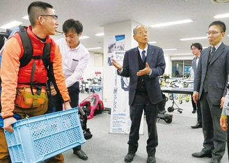 同社のマッスルスーツを体験(左)。中央が菊池社長