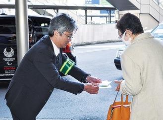 JR八王子駅前で「料金改定」を知らせるチラシを配布するタクシー会社の担当者。新しい料金体系では乗車距離によって従来の運賃より高くなるケースがあるという。「タクシー乗務員の確保と労働条件の改善を図るためです。ご理解頂ければと思います」