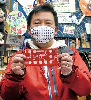 オリジナルマスクを手にする中川さん。店のフェイスブック(https://ja-jp.facebook.com/matsuriya)に記事をあげている