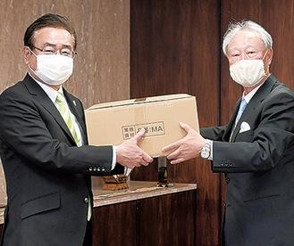 マスクを手渡す松山社長=右(提供写真)