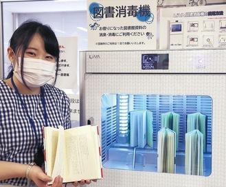 稼動時の図書消毒器。本を持つのは図書館職員の須田菜那恵さん