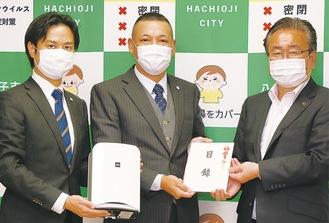 受領式の様子。右から石森孝志市長、山下代表、楠田正季専務