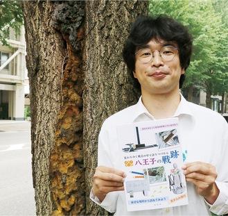 ガイドブックを持つ編集担当の同社の増沢航さん。同社前の甲州街道のいちょう並木は空襲の熱で被害を受けた(ウレタン部分)戦災樹木だという