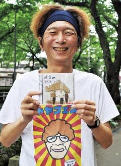 7月11日に発売したCDアルバムを持つ松崎さん