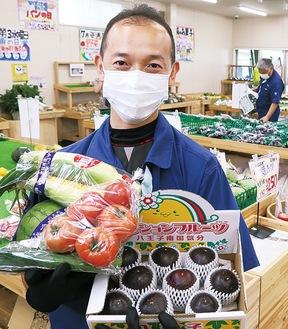 地元農家による旬の野菜を持つスタッフ