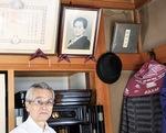 母親の遺影を背にする富田さん。壁にかかる帽子は一緒に会の活動を続け昨年亡くなった弟の遺品