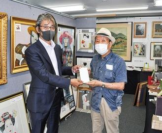 寄付金を手渡す神辺さん=右、受け取る尾川会長。ギャラリーにて
