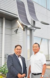設置された独立電源街路灯「リボーンライト」をバックにする水落社長(左)と平塚社長